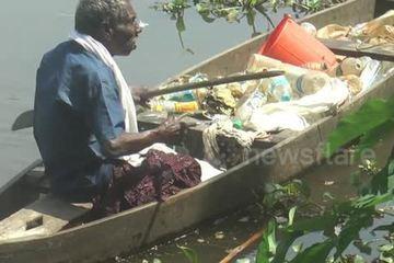 Ông lão liệt chân vẫn tình nguyện chèo thuyền để nhặt rác trên sông