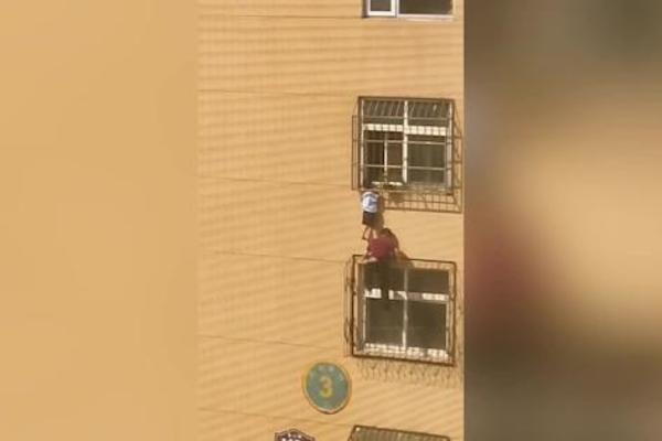 Bé trai lơ lửng bám ngoài chuồng cọp chung cư, 'người hùng' tay không trèo lên cứu